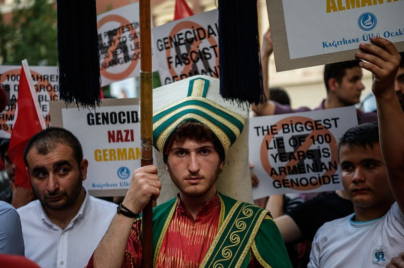 """Turkish nationalist protesters wearing Ottoman clothes shout slogans against Germany and hold placards on June 2, 2016 in front of the Germany consulate in Istanbul after German parliament labelled the World War I massacre of Armenians by Ottoman forces as genocide. Turkish President Recep Tayyip Erdogan on June 2 warned that the German parliament's recognition of World War I killings of Armenians by Ottoman forces as genocide would """"seriously affect"""" ties.  / AFP / OZAN KOSE        (Photo credit should read OZAN KOSE/AFP/Getty Images)"""