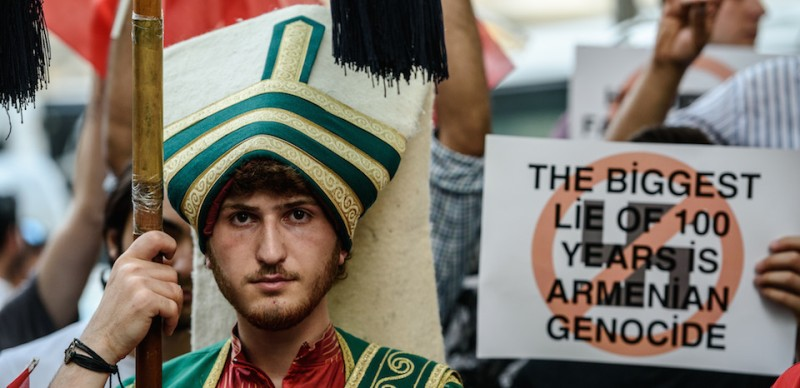 """A Turkish nationalist protester wearing Ottoman clothes holds placard during a protest against Germany on June 2, 2016 in front of the Germany consulate in Istanbul after German parliament labelled the World War I massacre of Armenians by Ottoman forces as genocide. Turkish President Recep Tayyip Erdogan on June 2 warned that the German parliament's recognition of World War I killings of Armenians by Ottoman forces as genocide would """"seriously affect"""" ties.  / AFP / OZAN KOSE        (Photo credit should read OZAN KOSE/AFP/Getty Images)"""