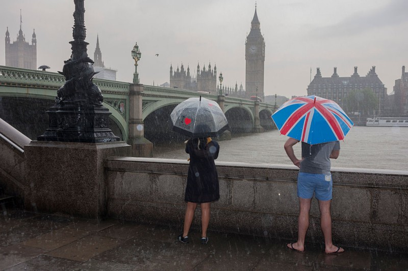 During a downpour, an afternoon of heavy rainfall in London, a wet man stands in a puddle overlooking the River Thames and parliament, from London's Southbank, on 7th June 2016. In the weeks before Britain goes to the polls to vote whether to stay or leave the EU community of nations, the man represents a poignant pause in the choices faced by Britons during turbulent times. (Photo by Richard Baker / in Pictures via Getty Images)