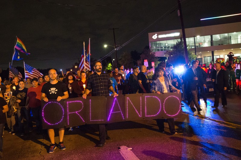 """Mourners hold an LED sign reading """"Dallas To Orlando"""" as they march during a vigil in Dallas, Texas, on June 12, 2016, for victims of the attack at Orlando's Pulse Nightclub in Orlando, Florida. Fifty people died when a gunman allegedly inspired by the Islamic State group opened fire inside a gay nightclub in Florida, in the worst terror attack on US soil since September 11, 2001. / AFP / Laura Buckman        (Photo credit should read LAURA BUCKMAN/AFP/Getty Images)"""