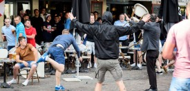 TOPSHOT - A man throws a chair as a small group of Russian men provoke a group of England supporters in the centre of Lille, on June 14, 2016, three days after Russia and England football fans clashed in the southern French city of Marseille during the Russia vs England, group B, Euro 2016 match.  / AFP / LEON NEAL        (Photo credit should read )