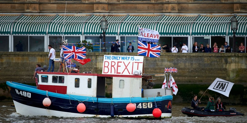 "A boat decorated with flags and banners from the 'Fishing for Leave' group that are campaigning for a 'leave' vote in the EU referendum sails by the British Houses of Parliament as part of a ""Brexit flotilla' on the river Thames in London on June 15, 2016. A Brexit flotilla of fishing boats sailed up the River Thames into London today with foghorns sounding, in a protest against EU fishing quotas by the campaign for Britain to leave the European Union. / AFP / NIKLAS HALLE'N        (Photo credit should read NIKLAS HALLE'N/AFP/Getty Images)"