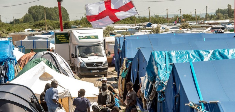 "Migrants stand below a flag of England inside the ""Jungle"" camp for migrants and refugees in Calais on June 24, 2016, the day after Britain voted to leave the EU. Eurosceptics are triumphant on June 24, 2016 after Britain voted to leave the EU and swiftly demanded referendums in their own countries, amid growing concerns Europe's hard-won unity may start to crumble away. Britons voted 52 percent to 48 percent to quit the bloc, a margin of more than one million votes, according to final results from Thursday's referendum.  / AFP / PHILIPPE HUGUEN        (Photo credit should read PHILIPPE HUGUEN/AFP/Getty Images)"