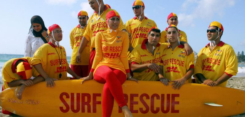 "Sydney, AUSTRALIA: Mecca Laa Laa (C) is wearing a full body covering known as the ""burqini"" and sits on a rescue board together with other Muslim life savers at Sydney's Cronulla beach, 04 February 2007.  Australia's first group of Muslim life savers hit the sand of Sydney's beaches a year after the mobs of whites attacked Lebanese Australian's in a bit to ""reclaim the beach"".  AFP PHOTO/Anoek DE GROOT (Photo credit should read ANOEK DE GROOT/AFP/Getty Images)"