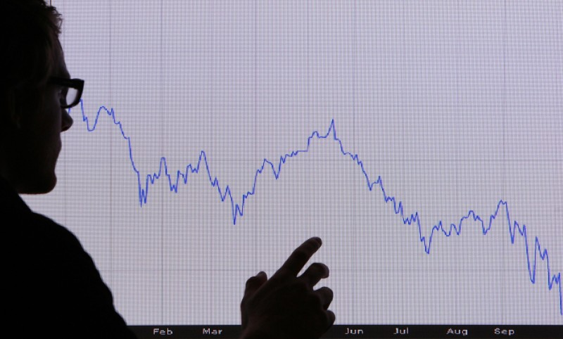 LONDON - OCTOBER 07:  In this photo illustration, a man looks at a graph representing the 12 month decline of the FTSE 100 share index on October 7, 2008 in London. Financial markets are still suffering large losses as the global banking crisis continued.  (Photo by Peter Macdiarmid/Getty Images)