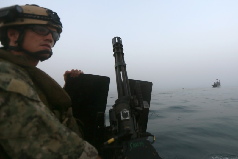 A US Navy crew mans a heavy machine gun on the deck of a Riverine Command Boat (RCB)  as it tails the USS Ponci somewhere in the Arabian Sea, on May 13, 2013, on the first day of the biggest mine countermeasures exercise in the Arabian Gulf. The US Navy along with other 40 nations are conducting the games.    AFP PHOTO/MARWAN NAAMANI        (Photo credit should read MARWAN NAAMANI/AFP/Getty Images)