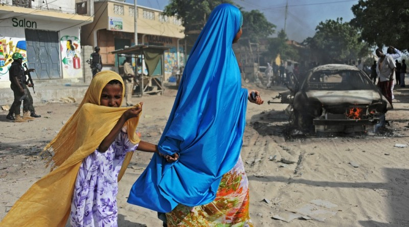 A mother and a child walk past the wreckage of a car bomb in the Wardhigley District, south of Mogadishu, on February 27, 2015. The bomb killed one person and injured another. AFP PHOTO/Mohamed Abdiwahab        (Photo credit should read MOHAMED ABDIWAHAB/AFP/Getty Images)