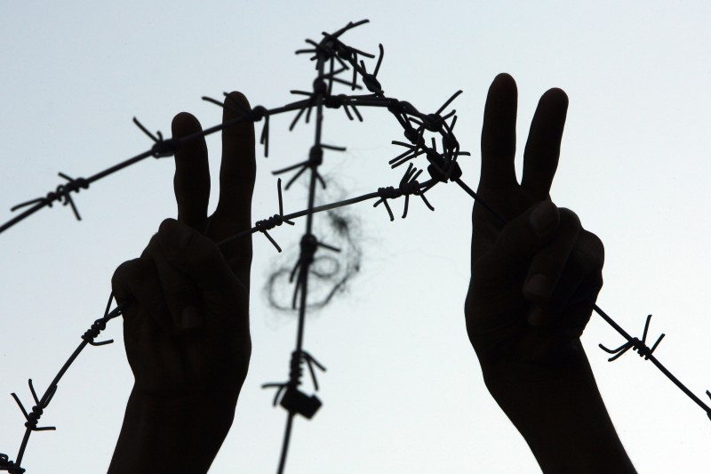 """A protestor flashes the """"V"""" for victory sign near barbed wire during a demonstration on November 01, 2010 calling for the release of Palestinian prisoners from Israeli jails, in Rafah, southern Gaza Strip.  AFP PHOTO/ SAID KHATIB (Photo credit should read SAID KHATIB/AFP/Getty Images)"""
