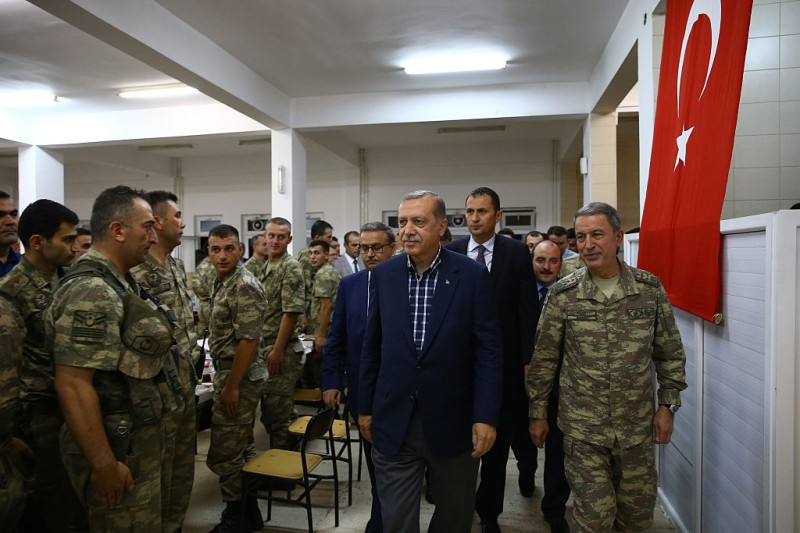 SIRNAK, TURKEY - JUNE 25: Turkish President Recep Tayyip Erdogan (2nd R) attends an Iftar (fast-breaking) Dinner during his visit at  172. Armored Brigade Command's 3. Tank Battalion campus  in Cizre District of Sirnak, Turkey on Islamic holy month Ramadan on June 25, 2016.  (Photo by Kayhan Ozer/Anadolu Agency/Getty Images)
