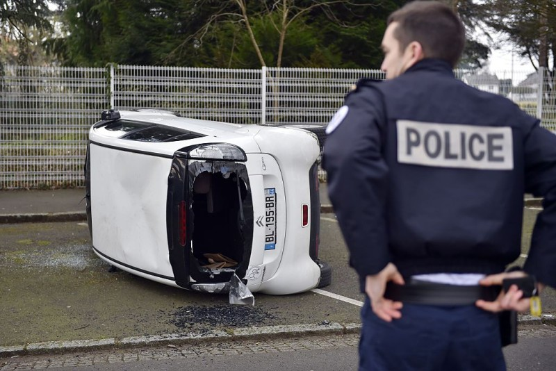 A police officer stands next to a damaged car near the Gaspard Monge La Chauviniere high school in Nantes, western France, on March 17, 2016 after it was overturned before a student demonstration as part of a nationwide day of protest against proposed labour reforms. High schools and universities were blocked on March 17 in Paris and in the provinces during demonstrations called by high school and student organisations opposed to deeply unpopular labour reforms, as thousands of youths took to the streets. / AFP / LOIC VENANCE        (Photo credit should read LOIC VENANCE/AFP/Getty Images)