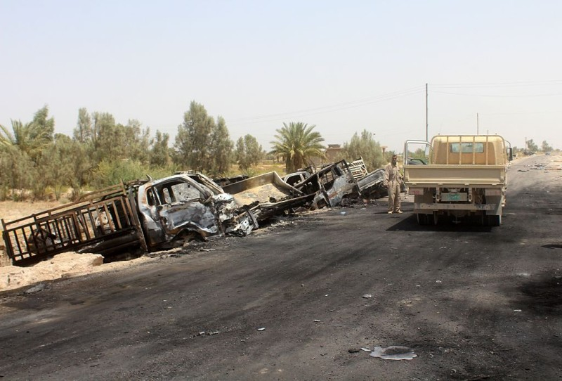 A member of the Iraqi government forces stands next to the charred vehicles on a road southwest of Fallujah on June 29, 2016 after Iraqi forces airstrikes destroyed 260 vehicles carrying militants from the Islamic State group trying to flee after their defeat in Fallujah. / AFP / MOADH AL-DULAIMI        (Photo credit should read MOADH AL-DULAIMI/AFP/Getty Images)