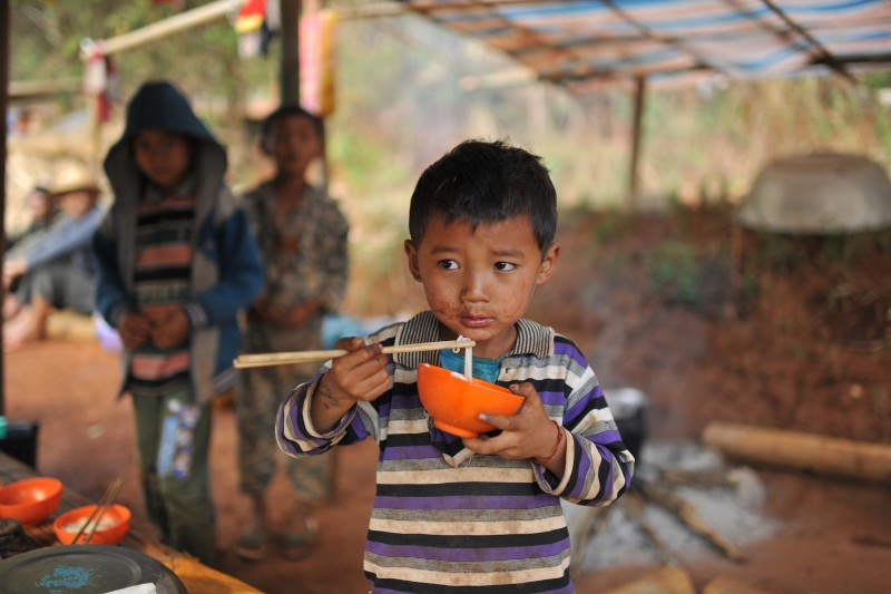 This picture taken on April 6, 2015 shows a Kokang refugee child eating noodles at their temporary shelter in the border area of China and Myanmar in Nansan township in Lincang, southwest China's Yunnan province. Mountainous Kokang is known for its strong bonds with China -- local people speak a Chinese dialect and China's yuan is the common currency and the conflict has tapped into long-standing nervousness in Myanmar about its giant northern neighbour. Tens of thousands of refugees have fled into China's Yunnan province since fighting in Kokang first flared up in early February. CHINA OUT AFP PHOTO        (Photo credit should read STR/AFP/Getty Images)