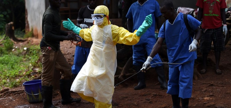 Health workers from the Sierra Leone's Red Cross Society Burial Team 7 are sprayed with desinfectant after removing a corpse from a house in Freetown on November 12, 2014. Red Cross has been providing a Safe and Digified Burial, with teams of 9 or 10 elements including a Beneficiary Communicator, in charge of adressing the community, explaining how to protect from the Ebola virus and reasuring the relatives that all due respect for the dead body and grant them access to the burial. AFP PHOTO/ FRANCISCO LEONG        (Photo credit should read FRANCISCO LEONG/AFP/Getty Images)