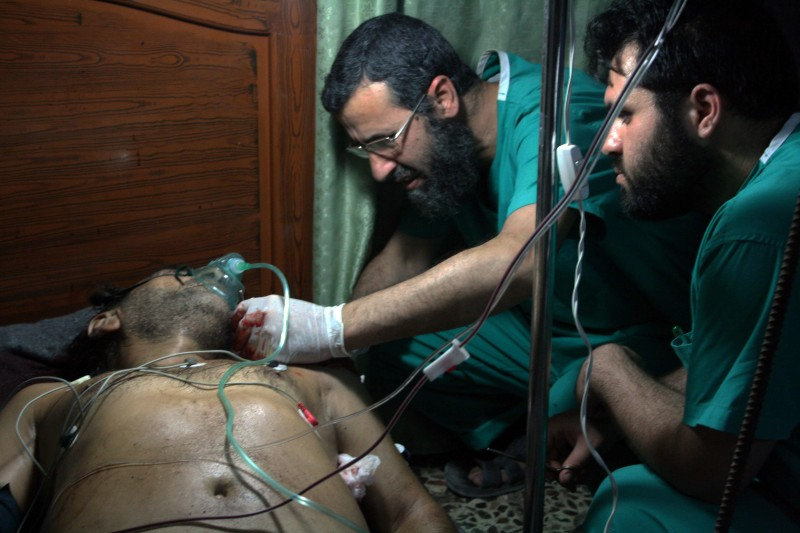 TO GO WITH STORY BY ANTONIO PAMPLIEGA Syrian doctors treat a wounded man in a field hospital in the besieged rebel-held city of Qusayr on July 10, 2012. Qusayr was once a city of 50,000, but its population has shrunk to around 10,000 as people have fled daily shelling and house-to-house fighting in President Bashar al-Assad's campaign to retake it. AFP PHOTO/ANTONIO PAMPLIEGA        (Photo credit should read Antonio Pampliega/AFP/GettyImages)