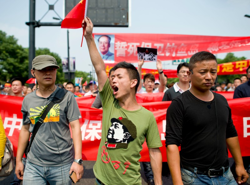 "Chinese demonstrators march with Chinese national flags and anti-Japan banners during a protest against Japan's ""nationalizing"" of Diaoyu Islands, also known as Senkaku in Japan, in Hangzhou, east China's Zhejiang province, on Septermber 18, 2012.Thousands of anti-Japan protesters rallied across China over a territorial row on September 18, a key historical anniversary, as Japanese firms including car giant Toyota shut or scaled back production.  CHINA OUT    AFP PHOTO        (Photo credit should read STR/AFP/GettyImages)"