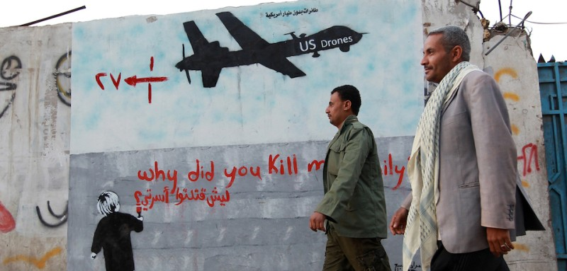 "Yemeni men walk past a mural depicting a US drone and reading "" Why did you kill my family"" on December 13, 2013 in the capital Sanaa. A drone strike on a wedding convoy in Yemen killed 17 people, mostly civilians, medical and security sources said, adding grist to mounting criticism of the US drone war.  AFP PHOTO/ MOHAMMED HUWAIS        (Photo credit should read MOHAMMED HUWAIS/AFP/Getty Images)"