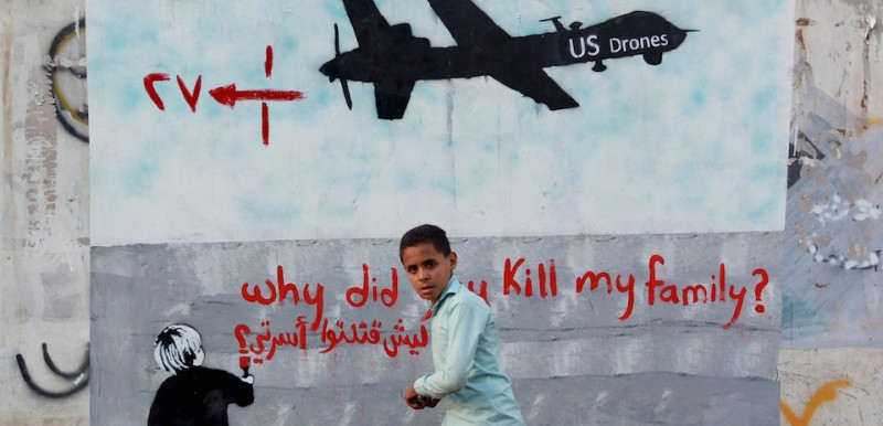 "A Yemeni boy walks past a mural depicting a U.S. drone and reading ""Why did you kill my family?"" in the capital Sanaa on Dec. 13, 2013."