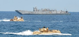 """US Marines amphibious assault vehicles (AAV) speed past a landing ship during an amphibious landing exercise on a beach at San Antonio in Zambales province on April 21, 2015, as part of annual Philippine-US joint maneuvers some 220 kilometres (137 miles) east of the Scarborough Shoal in the South China Sea. The Philippines voiced alarm April 20 about Chinese """"aggressiveness"""" in disputed regional waters as it launched giant war games with the United States that were partly aimed as a warning shot to Beijing. AFP PHOTO/TED ALJIBE        (Photo credit should read TED ALJIBE/AFP/Getty Images)"""