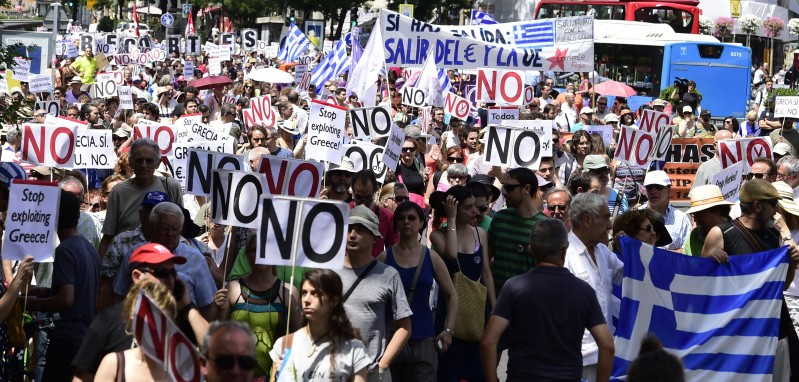 "People hold placards reading ""No"" during a demonstration in support of Greece, in Madrid on July 5, 2015. Today, nearly 10 million Greek voters take to the ballot booths to vote 'Yes' or 'No' in a referendum asking if they accept more austerity measures in return for bailout funds. The referendum on a deal with European governments, the European Union (EU) and International Monetary Fund (IMF), was called by Prime Minister Alexis Tsipras on the night of June 26-27.   AFP PHOTO/ JAVIER SORIANO        (Photo credit should read JAVIER SORIANO/AFP/Getty Images)"