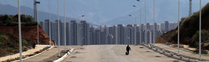 CHENGGONG, CHINA - NOVEMBER 20: (CHINA OUT) A man walks along a street on November 20, 2013 in Chenggong, Yunnan Province of China. Chenggong is a satellite city located just south of Kunming. As of 2012, much of the newly constructed housing in Chenggong is still unoccupied, and it is reportedly one of the largest ghost towns in Asia. According to a China Youth Daily report in July, at least 12 such ghost cities across the country have been found. Besides the best known of these - Ordos in North China's Inner Mongolia Autonomous Region, the list also included Changzhou in Jiangsu, Zhengdong New Area in Henan Province, Shiyan in Hubei and Chenggong District of Kunming in Yunnan.  (Photo by VCG/VCG via Getty Images)