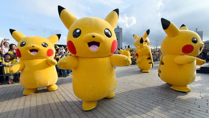 """Dozens of people dressed up as Pikachu, the famous character of Nintendo's videogame software Pokemon, dance with fans as the final of a nine-day """"Pikachu Outbreak"""" event takes place to attract summer vacationers in Yokohama, in suburban Tokyo, on August 16, 2015.       AFP PHOTO / Toru YAMANAKA        (Photo credit should read TORU YAMANAKA/AFP/Getty Images)"""