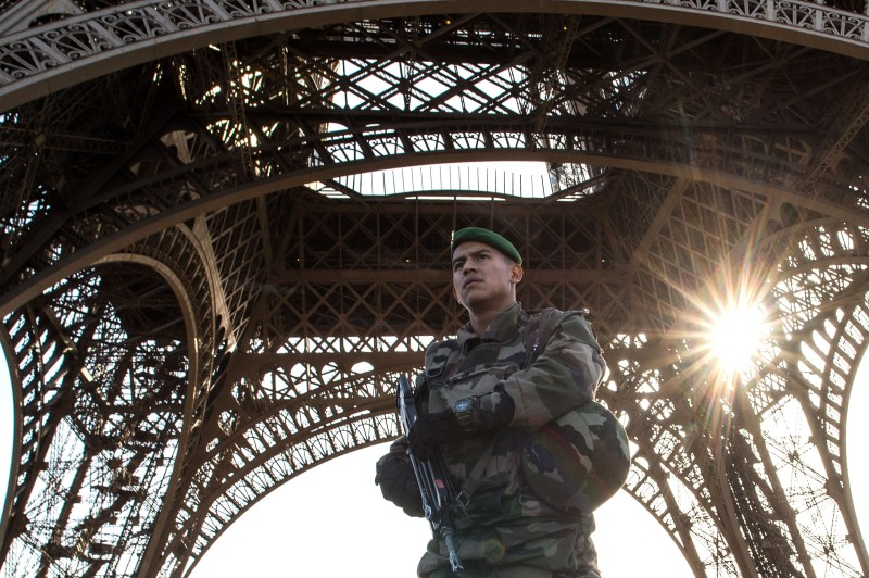 PARIS, FRANCE - NOVEMBER 15:  A French soldier stands guard at Eiffel Tower on November 15, 2015 in Paris, France. As France observes three days of national mourning members of the public continue to pay tribute to the victims of Friday's deadly attacks. A special service for the families of the victims and survivors is to be held at Paris's Notre Dame Cathedral later on Sunday.  (Photo by David Ramos/Getty Images)
