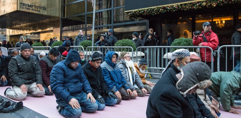 MIDTOWN MANHATTAN, NEW YORK, UNITED STATES - 2015/12/20: Muslim-American men from a local mosque pray in front of Trump Tower. Several hundred demonstrators rallied outside of Trump Tower at East 56th Street and Fifth Avenue in Manhattan to condemn Republican Presidential candidate Donald Trump's position on immigration rights; after rallying for nearly two hours, demonstrators marched to Herald Square. (Photo by )