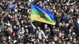 A man waves the Amazigh flag as thousands of mourners attend the funeral procession and burial of Hocine Ait-Ahmed, one of the fathers of Algeria's struggle for independence and a key opposition figure, in the Algerian village of Ait Ahmed on January 1, 2016. Ait-Ahmed's remains arrived in Algiers from Switzerland, where he died at the age of 89, for a state funeral the previous day before being transferred to his home village for his burial. The Amazighs, or Berbers, are the ethnicity indigenous to North Africa west of the Nile Valley.   / AFP / FAROUK BATICHE        (Photo credit should read FAROUK BATICHE/AFP/Getty Images)