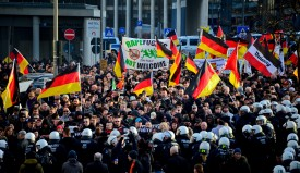 COLOGNE, GERMANY - JANUARY 09:  Protesters wave German flags, alongside a banner saying 'Rapefugees Not Welcome' as supporters of Pegida, Hogesa (Hooligans against Salafists)  and other right-wing populist groups protest against the New Year's Eve sex attacks on January 9, 2016 in Cologne, Germany. Over 100 women have filed charges of sexual molestation, robbery and in two cases, rape, stemming from aggressive groping and other behavior by gangs of drunken men described as Arab or North African at Hauptbahnhof on New Year's Eve. Police have recently stated that at least some of the men identified so far are refugees, which is feeding the propaganda of right-wing groups opposed to Germany's open-door refugee policy. Germany took in approximately 1.1 million migrants and refugees in 2015.  (Photo by Sascha Schuermann/Getty Images)