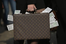 BERLIN, GERMANY - APRIL 13:  An activist clutching a suitcase stuffed with fake money demands greater trasparency in new legislation following the ongoing Panama Papers affair on April 13, 2016 in Berlin, Germany. Police in Panama have reportedly raided the offices of Mossack Fonseca, the law-firm accused of facilitating large-scale offshore tax evasion for thousands of its clients.  (Photo by Sean Gallup/Getty Images)