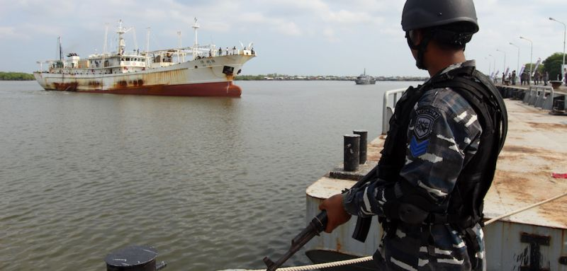 """This picture taken on April 23, 2016 shows a member of the Indonesian navy standing before the Chinese trawler """"Hua Li-8"""" (L) in Belawan, North Sumatra. Indonesian warships have detained a Chinese trawler allegedly operating illegally in Indonesian waters, just weeks after a confrontation between vessels from the two countries caused tensions, the navy said on April 24. / AFP / ABIMATA HASIBUAN        (Photo credit should read ABIMATA HASIBUAN/AFP/Getty Images)"""