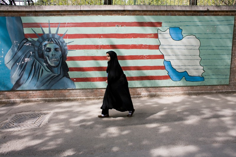 "A young Iranian girl wearing chador passing the murals at the former US embassy in Tehran, now referred as US Den of Espionage. The murals are affirming the evil of the ""Great Satan"" (the USA). (Photo by In Pictures Ltd./Corbis via Getty Images)"