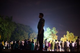 """TOPSHOT - A Bangladeshi policeman keeps guard near a group of peace activists who had come together to sing and light candles in a park following an attack and seige in Dhaka on July 3, 2016.  Bangladesh said July 3 the attackers who slaughtered 20 hostages at a restaurant were well-educated followers of a homegrown militant outfit who found extremism """"fashionable"""", denying links to the Islamic State group. As the country held services to mourn the victims of the siege in Dhaka, details emerged of how the attackers spared the lives of Muslims while herding foreigners to their deaths. / AFP / ROBERTO SCHMIDT        (Photo credit should read ROBERTO SCHMIDT/AFP/Getty Images)"""