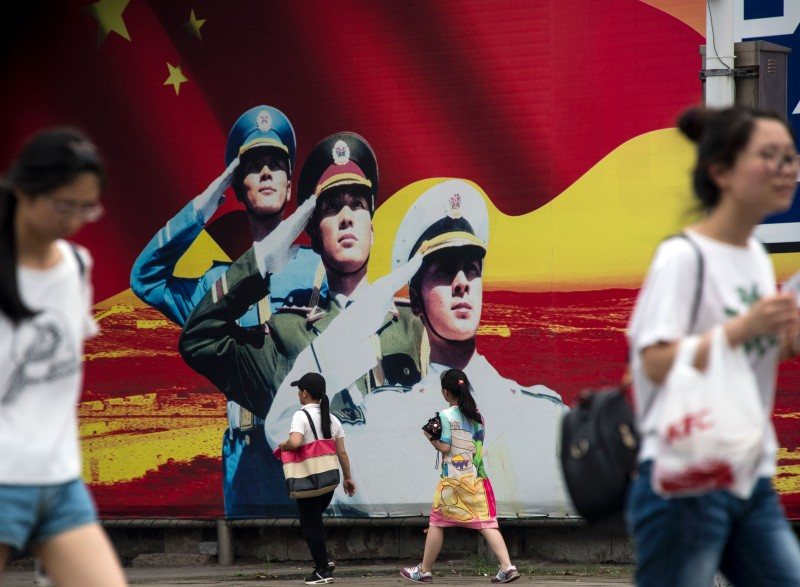 Pedestrians pass a military propaganda poster on a street in Shanghai on July 12, 2016.  Beijing braced on July 12 for an international tribunal's ruling on the South China Sea, where it has expansive territorial claims, with all eyes watching for the Asian giant's reaction on the ground or in the water. Beijing claims sovereignty over almost the whole of the South China Sea, on the basis of a segmented line that first appeared on Chinese maps in the 1940s, pitting it against several neighbours. / AFP / JOHANNES EISELE        (Photo credit should read JOHANNES EISELE/AFP/Getty Images)