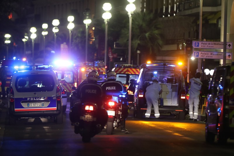 Police officers and rescue workers arrive at the scene of an attack on July 14, 2016, after a van ploughed into a crowd leaving a fireworks display in the French Riviera town of Nice. The mayor of the French city of Nice said dozens of people were likely killed after a van rammed into a crowd marking Bastille Day in the French Riviera resort today and urged residents to stay indoors.  / AFP / VALERY HACHE        (Photo credit should read VALERY HACHE/AFP/Getty Images)