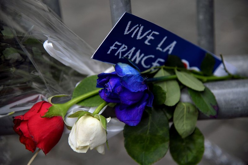 """TOPSHOT - A sign reading """"Long live France"""" is placed near roses in the colors of the French flag at a makeshift memorial in front of the French Embassy in Rome on July 15, 2016, in honour of the victims of an attack in Nice the day before that left at least 84 people dead. A Tunisian-born man zigzagged a truck through a crowd celebrating Bastille Day in the French city of Nice, killing at least 84 and injuring dozens of children in what President Francois Hollande on July 15 called a """"terrorist"""" attack. / AFP / TIZIANA FABI        (Photo credit should read TIZIANA FABI/AFP/Getty Images)"""