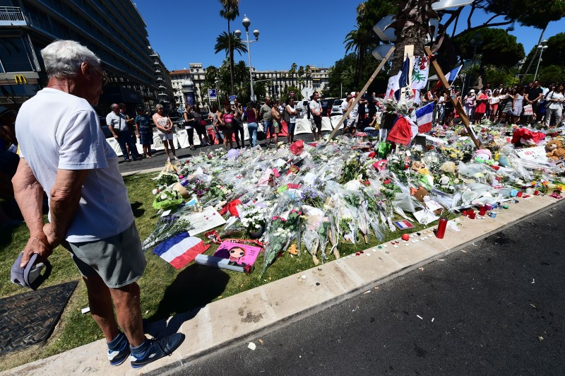 A man stands on July 16, 2016 near flowers and candles placed in tribute to the victims of the deadly Bastille Day attack in Nice. The Islamic State group claimed responsibility for the truck attack that killed 84 people in Nice on France's national holiday, a news service affiliated with the jihadists said on July 16. Tunisian Mohamed Lahouaiej-Bouhlel, 31, smashed a 19-tonne truck into a packed crowd of people in the Riviera city celebrating Bastille Day -- France's national day. / AFP / GIUSEPPE CACACE        (Photo credit should read GIUSEPPE CACACE/AFP/Getty Images)
