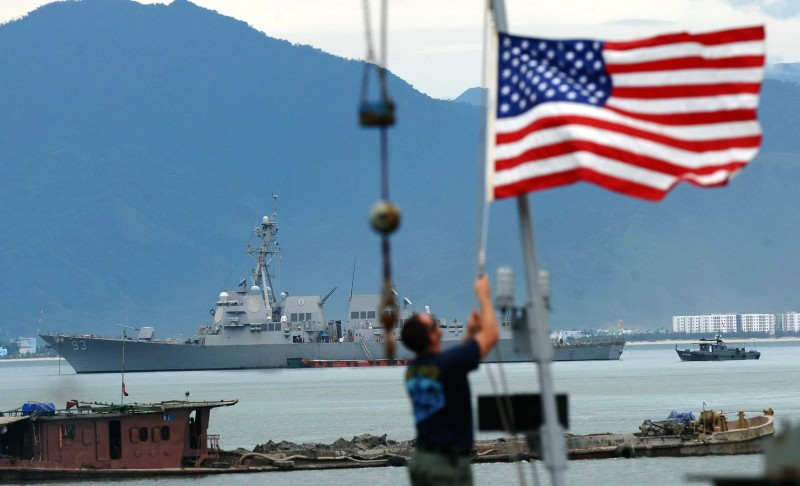 An US sailor raises the US flag on the USNS Safeguard as the USS Chung Hoon (in background) is also anchored at Tien Sa port in the central city of Da Nang on July 15, 2011. The port call by USSs Chung Hoon and Preble and USNS Safeguard is part of planned naval exchange activities between US and Vietnamese navies taking place amid high tensions over conflicting claims in the South China Sea. AFP PHOTO/HOANG DINH Nam (Photo credit should read HOANG DINH NAM/AFP/Getty Images)