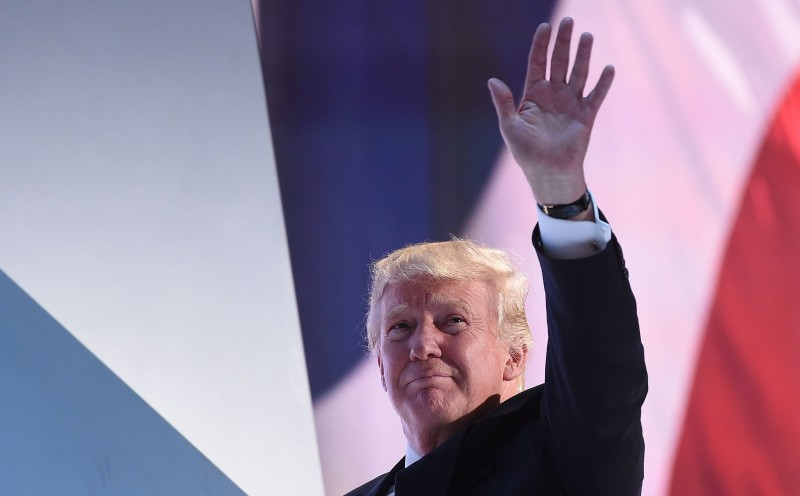 TOPSHOT - Republican Presidential candidate Donald Trump waves as he leaves the stage during the Republican National Convention at the Quicken Loans Arena in Cleveland, Ohio on July 20, 2016. The cost of the convention for the Republican Party will run some $64 million. The number of visitors expected in Cleveland is 50,000, including 15,000 journalists and 2,472 delegates (there are also 2,302 alternate delegates.)   / AFP / Robyn BECK        (Photo credit should read ROBYN BECK/AFP/Getty Images)