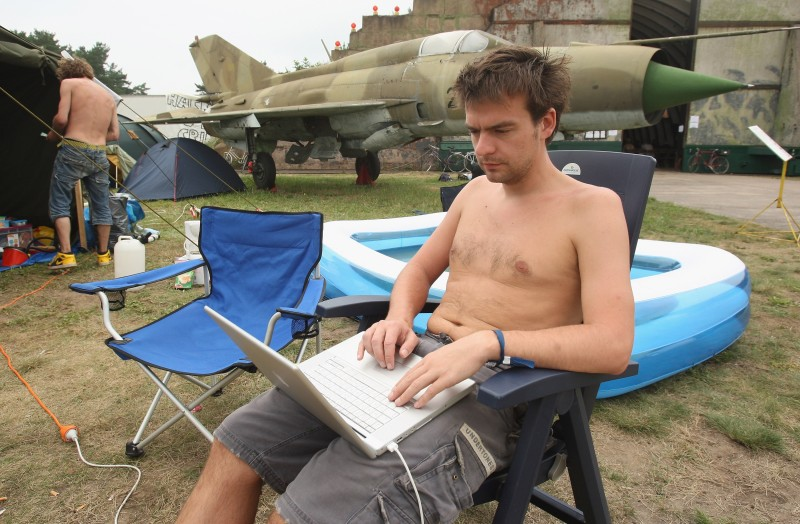 FINOWFURT, GERMANY - AUGUST 10:  A Dutch articipant at the Chaos Communication Camp 2007 works on his laptop next to a mothballed MiG fighter plane on the grounds of a former Soviet airbase near Berlin August 10, 2007 at Finowfurt, Germany. The camp brings together over a thousand computer hackers for four days to share software, ideas and discussions.  (Photo by Sean Gallup/Getty Images)