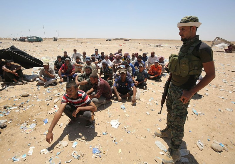 Iraqi men who fled the towns of al-Shirqat and Qayyarah during reported fighting between Iraqi government forces and jihadists of the Islamic State (IS) group, wait for inspection by security forces on the outskirts of al-Shirqat before being transferred to a camp for displaced people on July 27, 2016. IS overran large areas north and west of Baghdad in 2014, but Iraqi forces have since regained significant ground and are conducting operations to set the stage for the battle to recapture Mosul, the last IS-held city in the country.   / AFP / AHMAD AL-RUBAYE        (Photo credit should read AHMAD AL-RUBAYE/AFP/Getty Images)