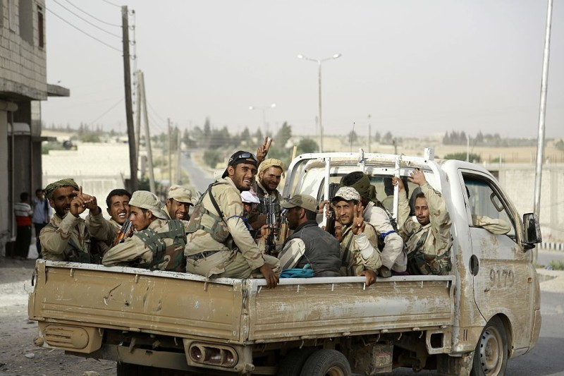 Fighters from Syria's Manbij military council sit on June 15, 2016 in the back of a pickup truck on the outskirts of the northern Syrian town of Manbij, which is held by jihadists of the Islamic State (IS) group, during an operation to try to retake the town. Hundreds of civilians escaped the IS stronghold of Manbij in nearby Aleppo province on June 12, helped by a US-backed Kurdish-Arab alliance surrounding the town. Tens of thousands had been trapped inside Manbij after the alliance encircled the town on June 10 in a major blow to the jihadist group controlling it.     / AFP / DELIL SOULEIMAN        (Photo credit should read DELIL SOULEIMAN/AFP/Getty Images)