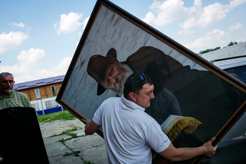 A member of the Jewish community takes out a portrait of the Russian-born Rabbi Menachem Mendel Schneerson from the Anatevka synagogue.