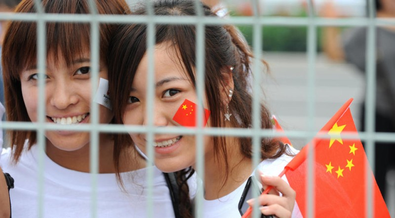 "Girls smile in front of the fence of the National Stadium, also known as the ""Bird's Nest"" after bying Chinese and Olympic flags in Beijing on August 6, 2008, two days before the opening of the 2008 Beijing Olympic Games. The 2008 Beijing Olympic Games will be held in China from August 8 to 24. AFP PHOTO/Aamir QURESHI (Photo credit should read AAMIR QURESHI/AFP/Getty Images)"
