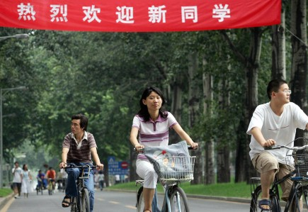 beijing, CHINA:  Chinese university students cycle on the campus of the pretigious Tsinghua University in Beijing 30 August 2006, with a banner welcoming the new students in the background.  Plagiarism is rampant at Chinese universities as academics are pushed to publish or perish, with their schools often covering up for them, as a recent survey of 160 Ph.D. holders found 60 percent had copied the work of others and the same percentage had paid in order to be published in academic journals.            AFP PHOTO  (Photo credit should read STR/AFP/Getty Images)