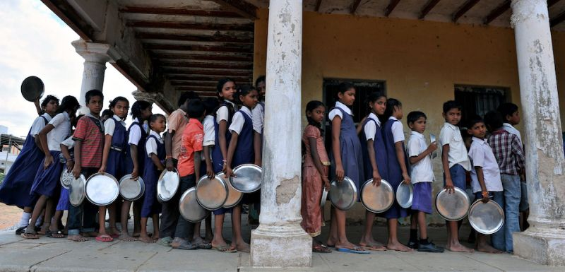 Indian schoolchildren wait in line for their mid-day meal at a government primary school in the outskirts of Hyderabad on June 13, 2011, on the opening day of the new academic year. The government of India's Andhra Pradesh state has introduced English as a second language from Class 1 onwards for the 2011-2012 academic year. India's National Knowledge Commission has admitted that no more than one percent of country's population uses English as a second language. AFP PHOTO/Noah SEELAM (Photo credit should read )