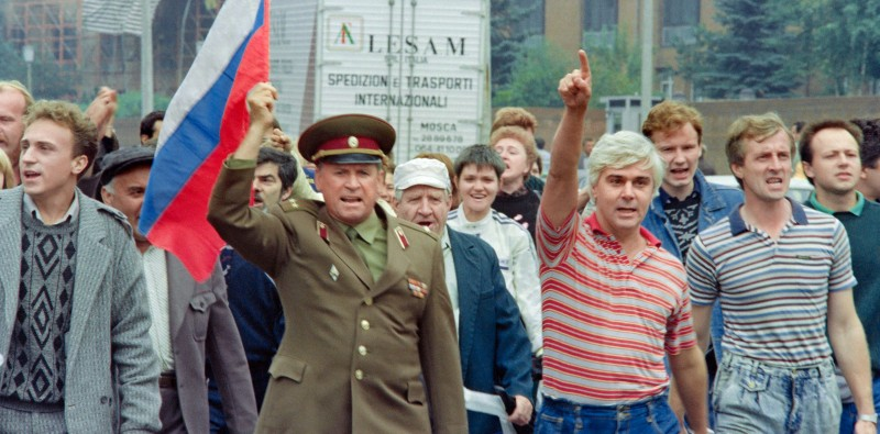 (FILES) A picture taken in Moscow on August 20, 1991 shows a group of Yeltsin supporters, including a Soviet colonel with the Russian flag, walking towards the Russian Parliament, as thousands of Muscovites are gathering around the building to support President of Russian Federation Boris Yeltsin to protest against the toppling of Soviet President Mikhail Gorbachev by communist hardliners early on August 19. AFP PHOTO / MICHAEL EVSTAFIEV        (Photo credit should read )