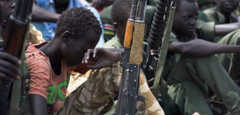 Young boys, children soldiers sit on February 10, 2015 with their rifles at a ceremony of the child soldiers disarmament, demobilisation and reintegration in Pibor oversawn by UNICEF and partners. UNICEF and its partners have overseen the release of another 300 children from the Cobra Faction armed group of former rebels of David Yau Yau. The children in Pibor, Jonglei State, surrendered their weapons and uniforms in a ceremony overseen by the South Sudan National Disarmament, Demobilization and Reintegration Commission, and the Cobra Faction and supported by UNICEF. They were to spend their first night in an interim care center where they will be provided with food, water and clothing. They will also have access to health and psychosocial services. AFP PHOTO/Charles LOMODONG / AFP / CHARLES LOMODONG        (Photo credit should read CHARLES LOMODONG/AFP/Getty Images)