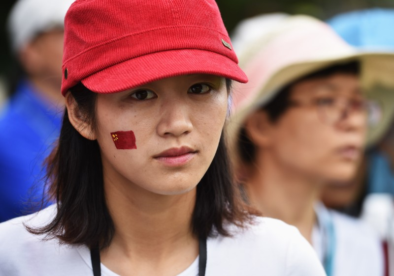 SHENZHEN, CHINA - APRIL 18:  A Chines girl with the Chinese flag painted on her face looks on during the third round of the Shenzhen International at Genzon Golf Club on April 18, 2015 in Shenzhen, China.  (Photo by Stuart Franklin/Getty Images)