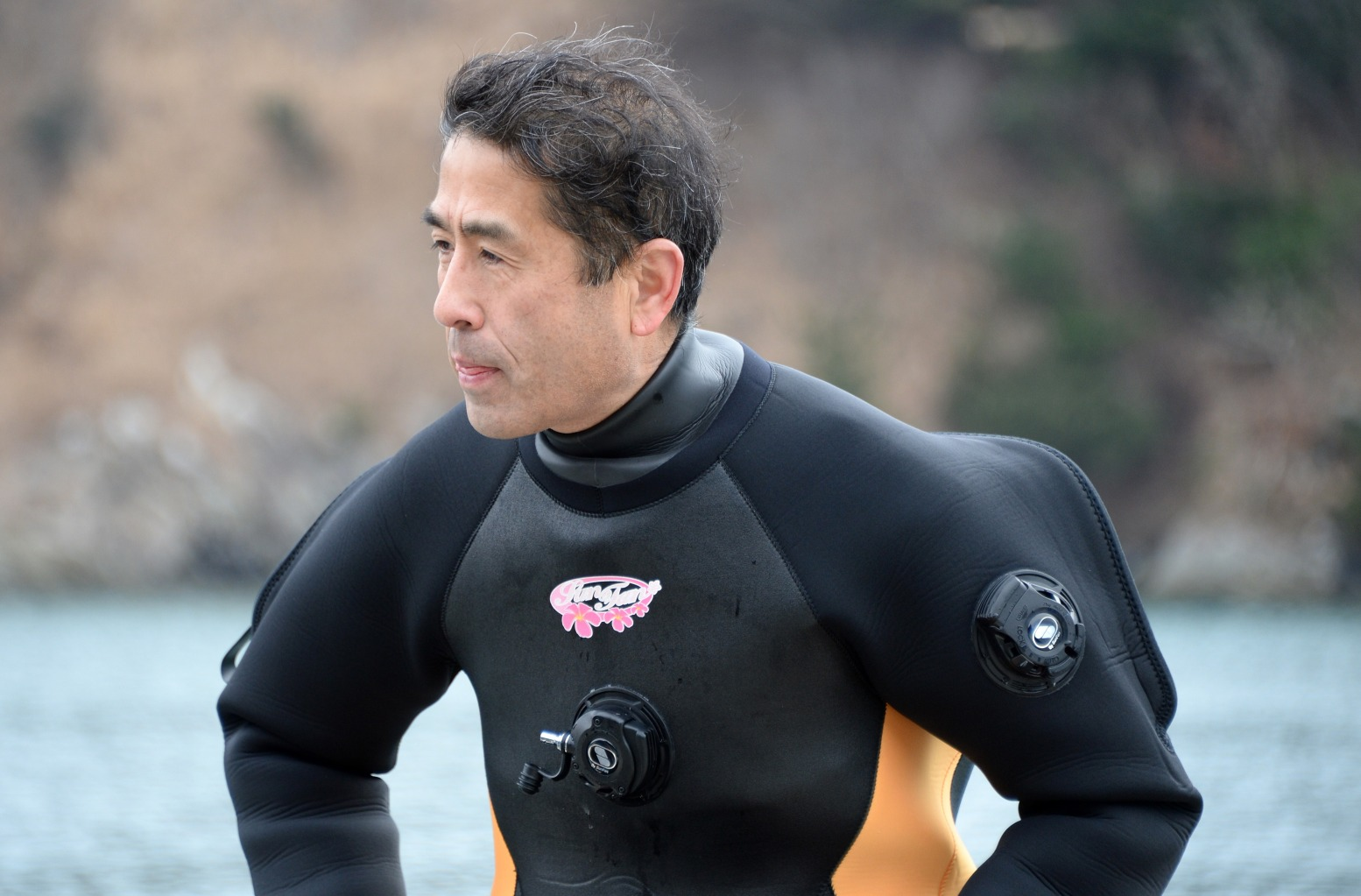 To go with story: Japan-Nuclear-Disaster-Diving,FEATURE by Harumi Ozawa Yasuo Takamatsu looks out to sea as he sits on the edge of a boat after a diving lesson in Onagawa, Miyagi Prefecture, on March 2, 2014. Te 57-year-old bus driver started taking scuba diving lessons in November to find his wife who is still missing after the 3/11 tsunami. AFP PHOTO/Toru YAMANAKA (Photo credit should read TORU YAMANAKA/AFP/Getty Images)